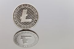 Solo Litecoin. A solo Litecoin coin reflected on a white background Stock Images