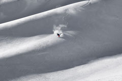 Solo lone skier putting down fresh first tracks on mountain ridg Royalty Free Stock Photography