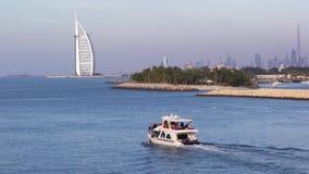 Solo móvil del pequeño yate el mar con el hotel de Burj Al Arab visto en el fondo en febrero 12,2017 almacen de metraje de vídeo