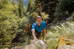 Solo man climbing a rock in the forest stock images