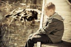 Solo muchacho en la chaqueta que se sienta en muelle Fotos de archivo libres de regalías
