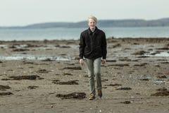 Solo muchacho rubio que camina en la playa afuera Fotos de archivo libres de regalías