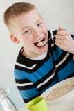 Solo niño que pone la harina de avena en su boca Imagen de archivo
