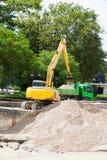 Solo ou areia da carga da máquina da máquina escavadora no corpo do caminhão Imagem de Stock Royalty Free