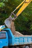 Solo ou areia da carga da máquina da máquina escavadora no corpo do caminhão Fotografia de Stock