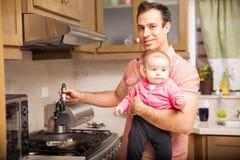 Solo padre que cocina el desayuno con un bebé Foto de archivo libre de regalías