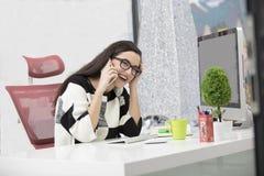 Solo propietario de negocio de sexo femenino feliz con sonrisa y las lentes en el teléfono y el trabajo en el equipo de escritori imagen de archivo libre de regalías