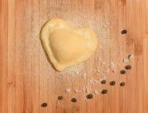 Solo raviolo fresco, hecho a mano en la forma del corazón con pocos granos de la pimienta negra y sal gruesa Foto de archivo libre de regalías