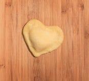 Solo raviolo fresco, hecho a mano en la forma del corazón, cubierto con la harina y puesto en la tabla de madera Imágenes de archivo libres de regalías
