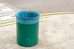 Solo recipiente para residuos verde vacío con la bolsa de plástico azul nueva y limpia en el área pública fotos de archivo