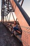 Solo ribelle della ragazza teenager si siede pensively sul parapetto della costruzione di ponte d'acciaio in bacini abbandonati n immagini stock libere da diritti