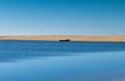 Solo roddbåt som förtöjas på Sandy Beach Arkivfoto
