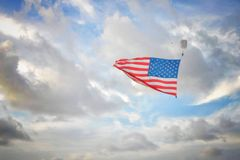 Solo skydiver carries an American flag against a cloudy sky stock images