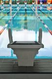 Solo starting block. A solitary starting block facing the empty olympic size swimming pool Royalty Free Stock Photography