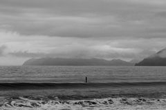 Solo SUP Boarder in Black and White. A lone stand up paddle (SUP) surfer bobs up and down in the cold Alaskan ocean waiting for a wave Stock Photos