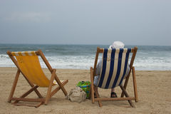 Solo vacation. Old man sitting in a deckchair  facing the ocean Stock Photography