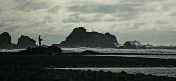 Solo visser op afgezonderd strand stock foto's