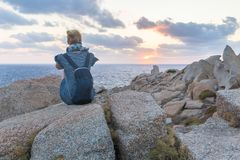 Solo young female traveler watches a beautiful sunset on spectacular rocks of Capo Testa, Sardinia, Italy. Royalty Free Stock Images