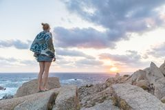 Solo young female traveler watches a beautiful sunset on spectacular rocks of Capo Testa, Sardinia, Italy. Royalty Free Stock Photo