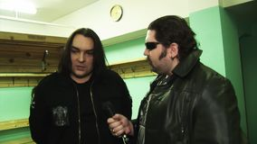 Soloist rock band Kukryniksy Alex Gorshenev give interview at backstage to man in leather jacket. Nightclub stock footage
