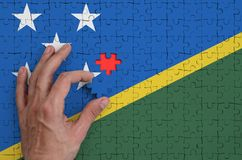 Solomon Islands flag is depicted on a puzzle, which the man`s hand completes to fold.  royalty free illustration
