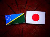 Solomon Islands flag with Japanese flag on a tree stump isolated Royalty Free Stock Images