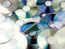 Solomon Islands flag on top of CD and DVD pile isolated on white. Solomon Islands flag on top of CD and DVD pile isolated Royalty Free Stock Photography