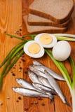 Solona sardeli, jajka, chleba i wiosny cebula na drewnie, zdjęcie stock
