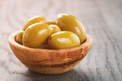 Solone gigantyczne zielone oliwki w oliwnym pucharze na drewnianym stole obraz stock