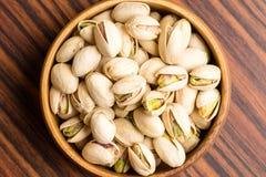 Solone pistacjowe dokrętki w drewnianym pucharze Obraz Stock