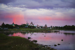 Solovetsky monastery at sunset in the rainbow that is reflected on the surface of the sea in the bay. Royalty Free Stock Photo