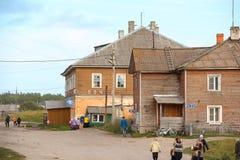 Solovky, RYSSLAND - Augusti 25 2015, den norr byn med träbaracker med stolpen - kontor och folk som går på grusvägen, på Augusti  Royaltyfria Foton