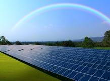 Solpaneler med härlig regnbågehimmel Arkivfoton