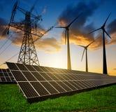 Solpaneler med vindturbiner och elektricitetspylonen royaltyfri foto