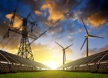 Solpaneler med vindturbiner och elektricitetspylonen på solnedgången arkivbild