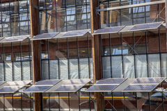 Solpaneler på framdelen av en kontorsbyggnad som en lösning fo Arkivbild