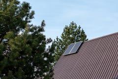 Solpaneler som installeras på taket i ett landshus på bakgrunden av gröna träd m?nga begreppsekologibilder mer min portf?lj arkivbilder