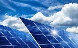 Solpaneler som reflekterar solen och molnen Arkivfoto