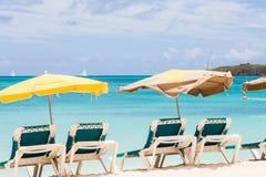 Solparaplyer över gräsplanstolar på stranden Fotografering för Bildbyråer