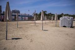 Solparaplyer p? stranden med sols?ngar royaltyfri fotografi