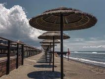 Solparaplyer ställde upp på en strand arkivfoton