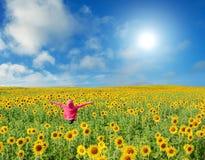 Solrosfält med den unga kvinnan Arkivbilder