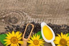 Solrosolja, frö och blomma på träbakgrund med kopieringsutrymme för din text Top beskådar royaltyfri foto