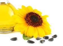 Solrosolja i den glass tillbringaren, frö och blomman som isoleras på vit bakgrund Arkivbild