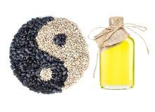 Solrosolja i en tillverkad glasflaska och en yin och ett yang symbol som göras av frö på vit backgound arkivfoto