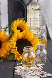 Solrosolja och stora gula blommor nära fönstret Olja i buteljera Utan en peel av solrosfrö för fotostruktur för abstrakt bakgrund Royaltyfri Fotografi