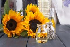 Solrosolja och stora gula blommor nära fönstret Olja i buteljera Utan en peel av solrosfrö för fotostruktur för abstrakt bakgrund Fotografering för Bildbyråer