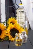 Solrosolja och stora gula blommor nära fönstret Olja i buteljera Utan en peel av solrosfrö för fotostruktur för abstrakt bakgrund Royaltyfria Bilder