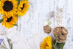 Solrosolja och stora gula blommor Olja i buteljera Utan peelen av solrosfrö och kakor vitt trä för bakgrund Arkivfoton