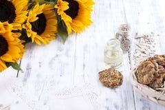 Solrosolja och stora gula blommor Olja i buteljera Utan peelen av solrosfrö och kakor vitt trä för bakgrund Arkivbild